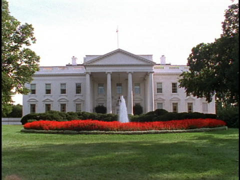 A fountain bubbles in the middle of a garden in front of the White House Footage
