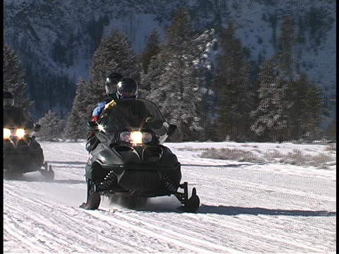 Snowmobiles drive down a snow packed road Stock Video Footage
