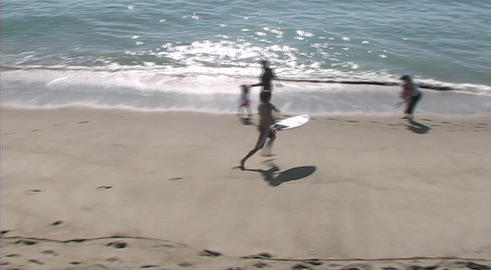 A young man practices waveboarding on a California beach... Stock Video Footage