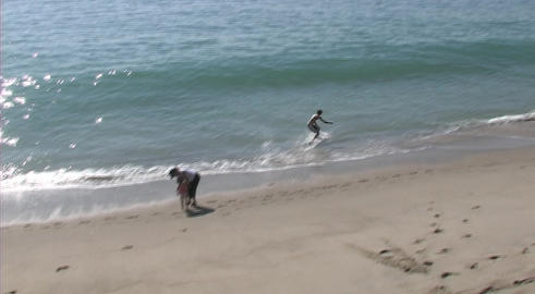 A young man practices waveboarding on a California beach and wipes out Footage