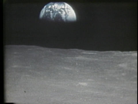 A half Earth shines over the horizon of the moon Stock Video Footage