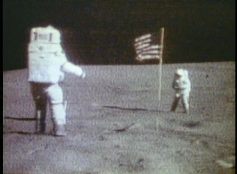 Astronauts walk on the moon with the American flag... Stock Video Footage