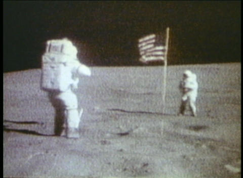 Astronauts walk on the moon with the American flag planted in the distance Footage