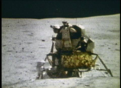 Long-shot of astronauts walking around Lunar Module on moon Stock Video Footage