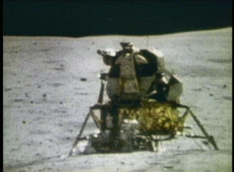 Long-shot of astronauts walking around Lunar Module on moon Footage