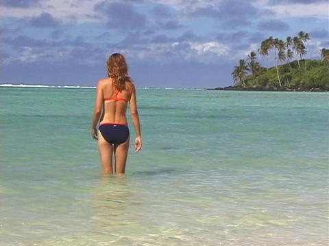 A vacationer wades into the ocean Stock Video Footage
