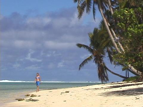 A woman strolls down a tropical beach Stock Video Footage