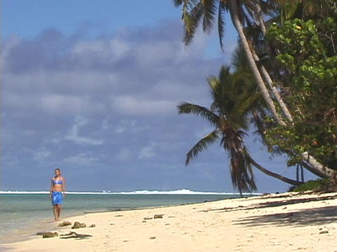 A woman strolls down a tropical beach Footage