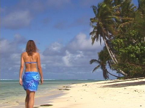 A women strolls across a tropical beach Stock Video Footage