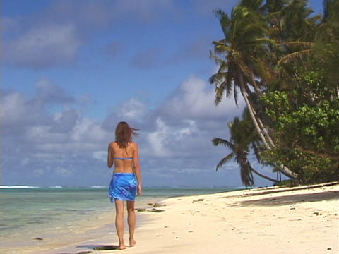 A women strolls across a tropical beach Footage