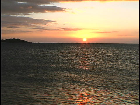 An orange sun hovers on the horizon at golden hour Stock Video Footage