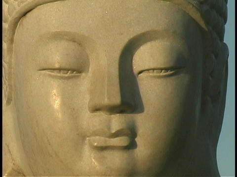 Light shines on a Buddha statue Stock Video Footage