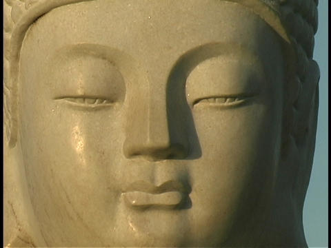 Light shines on a Buddha statue Footage
