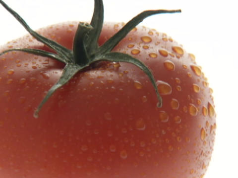 Water droplets glisten on a ripe, red tomato Stock Video Footage