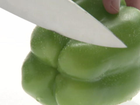 A person uses a knife to slice a green bell pepper Stock Video Footage