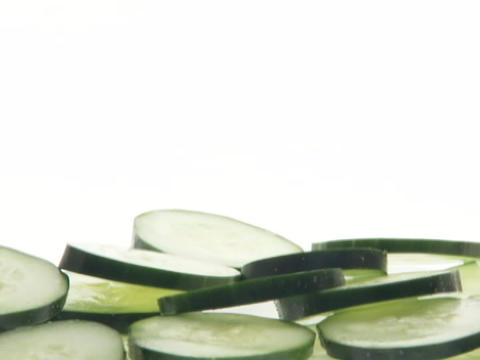 Slices of cucumbers fall into a pile Stock Video Footage