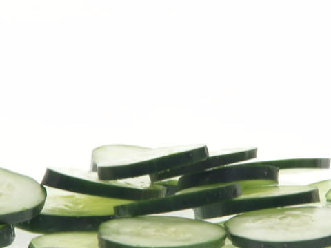Slices of cucumbers fall into a pile Live Action