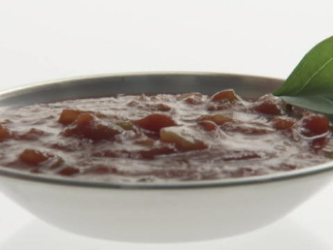 A person dips a chip into a bowl of salsa Footage