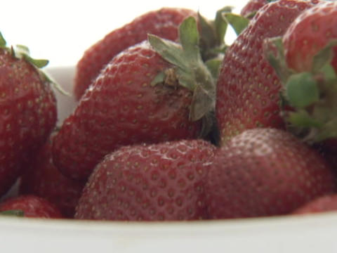 Red, ripe strawberries drop into a bowl Stock Video Footage