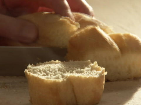 A knife cuts though a loaf of bread Stock Video Footage