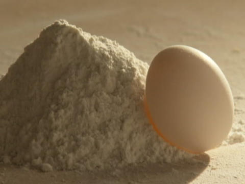 An egg and a pile of flour sit on a counter Footage