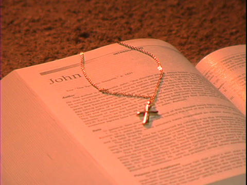 A gold cross rests in a bible over the book of John Footage