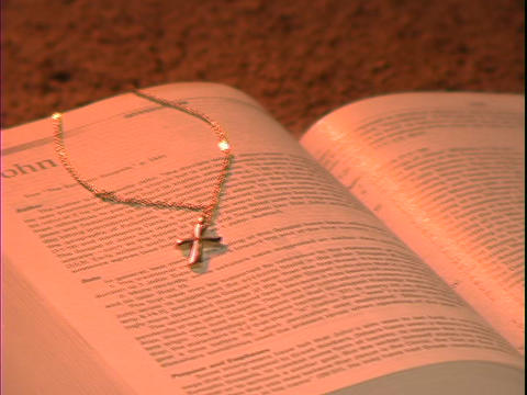 A gold cross rests on a Bible over the book of John Footage