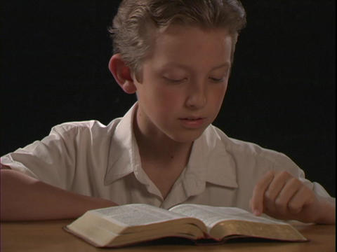 A young boy reads the Bible Live Action