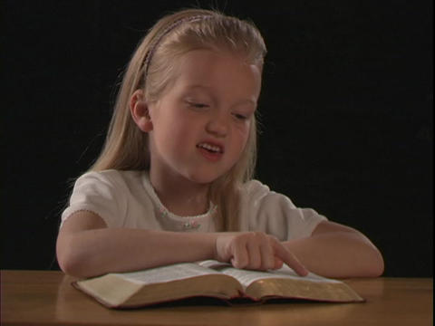 A young girl reads the Bible Stock Video Footage