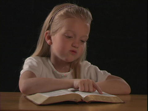A young girl reads the Bible Footage