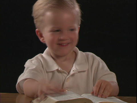 A little boy reads the Bible Footage