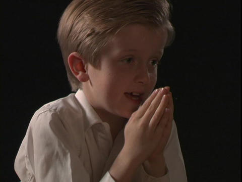 A young boy prays Footage