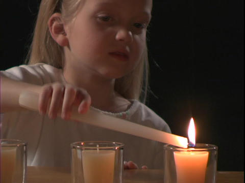 A young girl lights a candle Footage