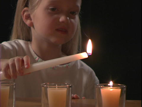 A young girl lights a candle Stock Video Footage