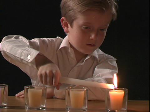 A young boy lights a candle Stock Video Footage