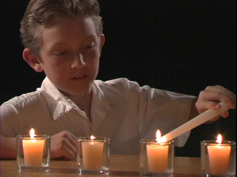 A boy lights candles Stock Video Footage