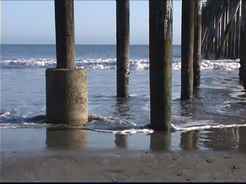 Ocean waves roll under a pier Footage