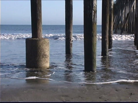 Ocean waves roll under a pier Stock Video Footage