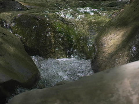 A stream flows over rocks Live Action