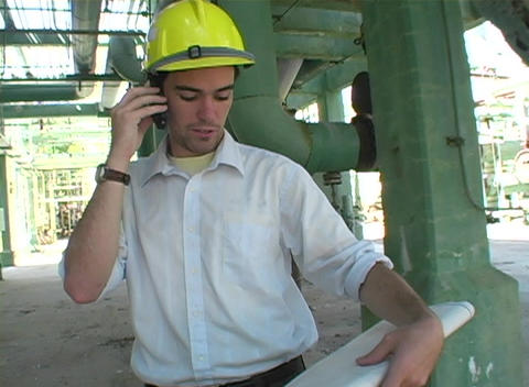 Tracking shot of a contractor talk on a cell phone while... Stock Video Footage