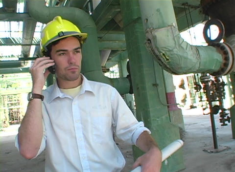 Tracking shot of a contractor talk on a cell phone while looking at blueprints Footage
