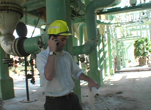 Following shot of a contractor looking at blueprints while talk on a cell phone Footage