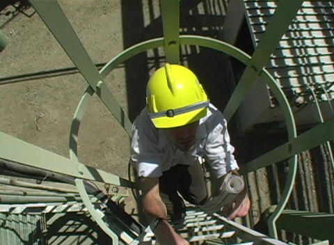 Tracking shot of a contractor climbing a fixed ladder with protective cage Footage
