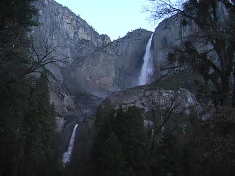 A waterfall flows over a cliff in Yosemite National Park,... Stock Video Footage