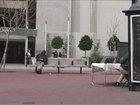 A homeless man sleeps on a park bench as pedestrians walk... Stock Video Footage