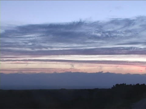 Clouds pass over a silhouetted landscape Stock Video Footage