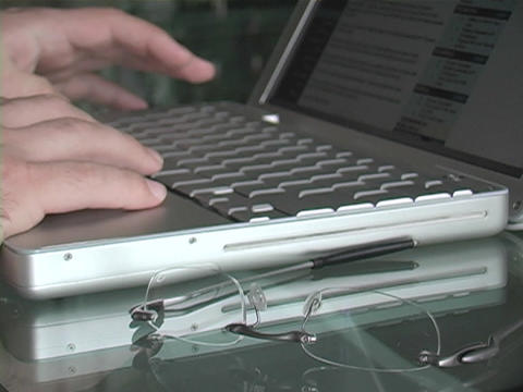 A man types on the keyboard of his laptop Stock Video Footage