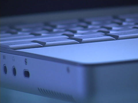 The base of a laptop computer is closely inspected Stock Video Footage