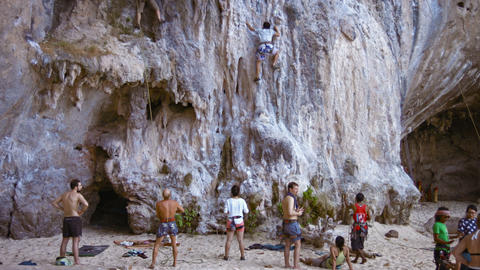 Brave tourist attempting to scale the limestone cliff face at Railay Beach. a po Footage