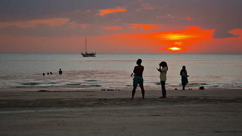 Tourists enyoying a romantic sunset over a popular. tropical beach in Langkawi Live Action